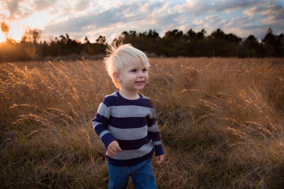 Child runs through grassy meadow in McGees Crossroads NC during a portrait session