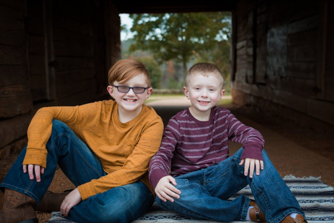 Two brothers sit on a blanket at Joyner Park in Wake Forest