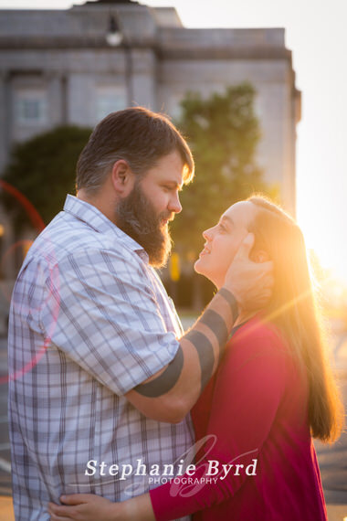 A man kisses his fiance in downtown Fayetteville during a sunsest glow photo session.