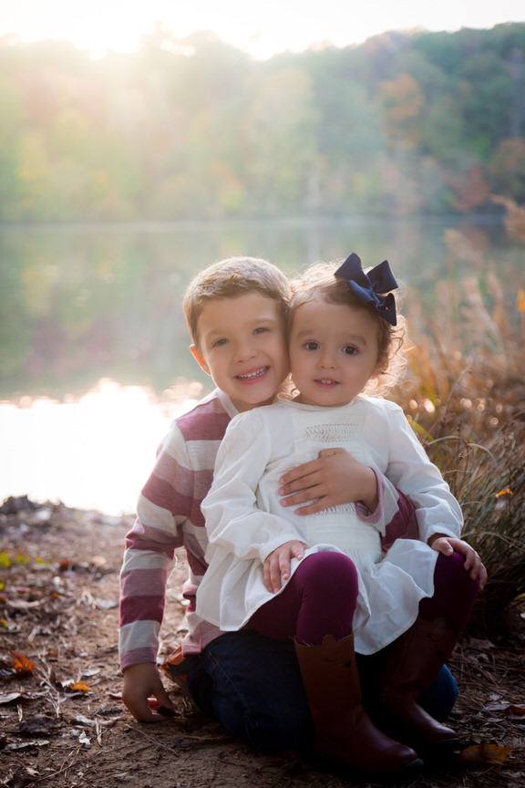 A boy holds his little sister in his lap as they smile together for pictures