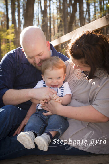 A dad tickles a baby during an outdoor morning photo session at Lake Benson Park in Wake County.