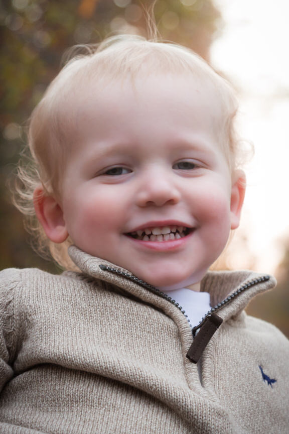 Little boy with wispy blonde hair wearing a brown sweater gives a big smile