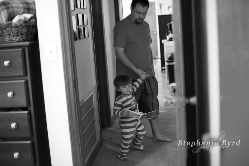 A toddler pulls Dad by the hand to go read his favorite book.