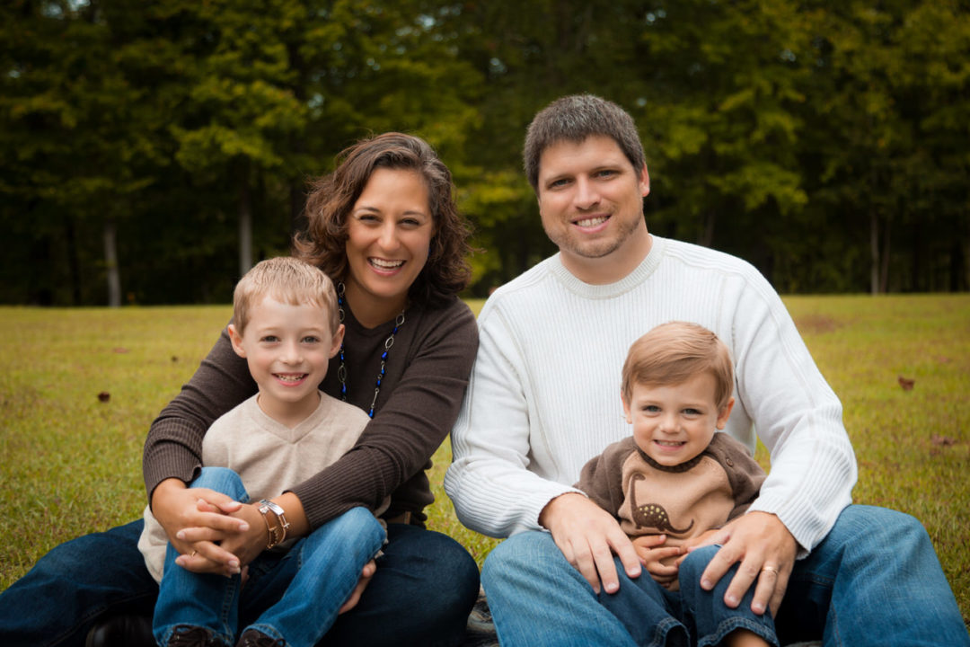 At a White Deer Park Garner photo session, two parents hold their little boys while sitting on the grass.