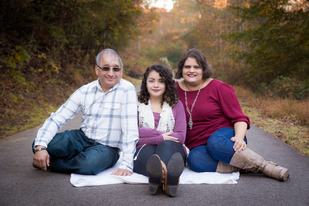 Mother, father, and daughter sit on a blanket at White Deer Park in Garner, NC